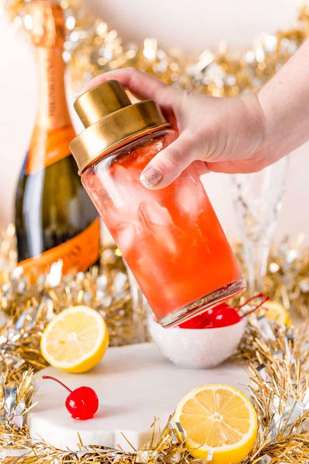 Cocktail shaker full of light red liquid.
