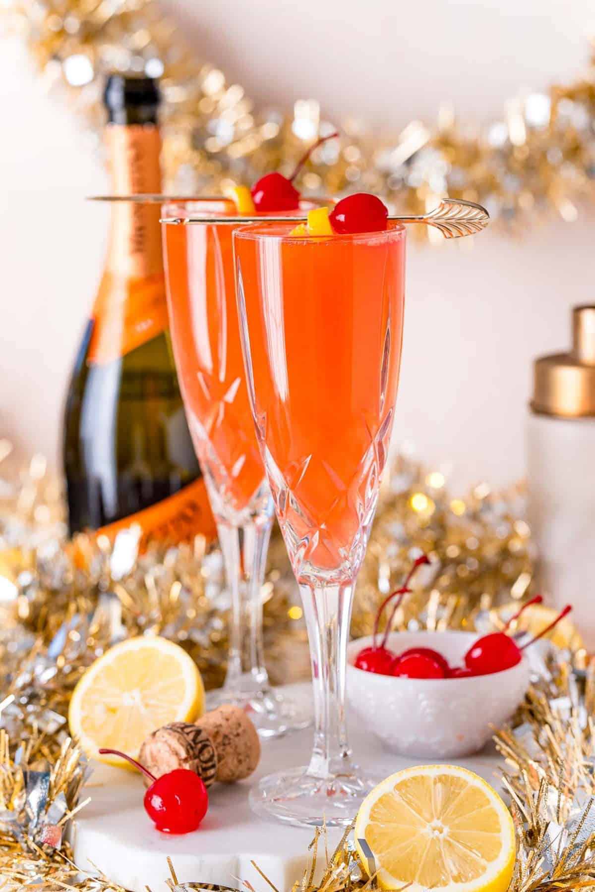Two champagne flutes with a light red drink garnished with cherries and lemon.