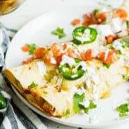 Two chicken enchiladas on a plate with verde sauce, pico de gallo, jalapenos, and sour cream.