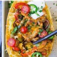 "Colorfully topped spaghetti squash half, text overlay reads ""chicken fajita stuffed spaghetti squash, rachelcooks.com"""