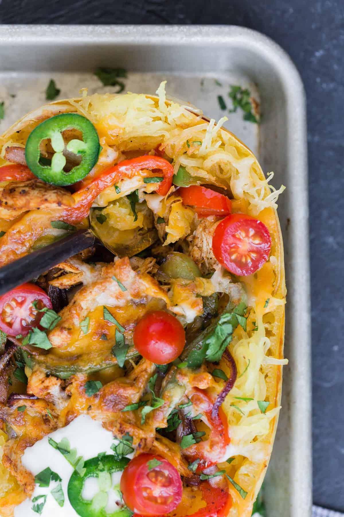 Close up of a chicken fajita stuffed spaghetti squash with toppings.