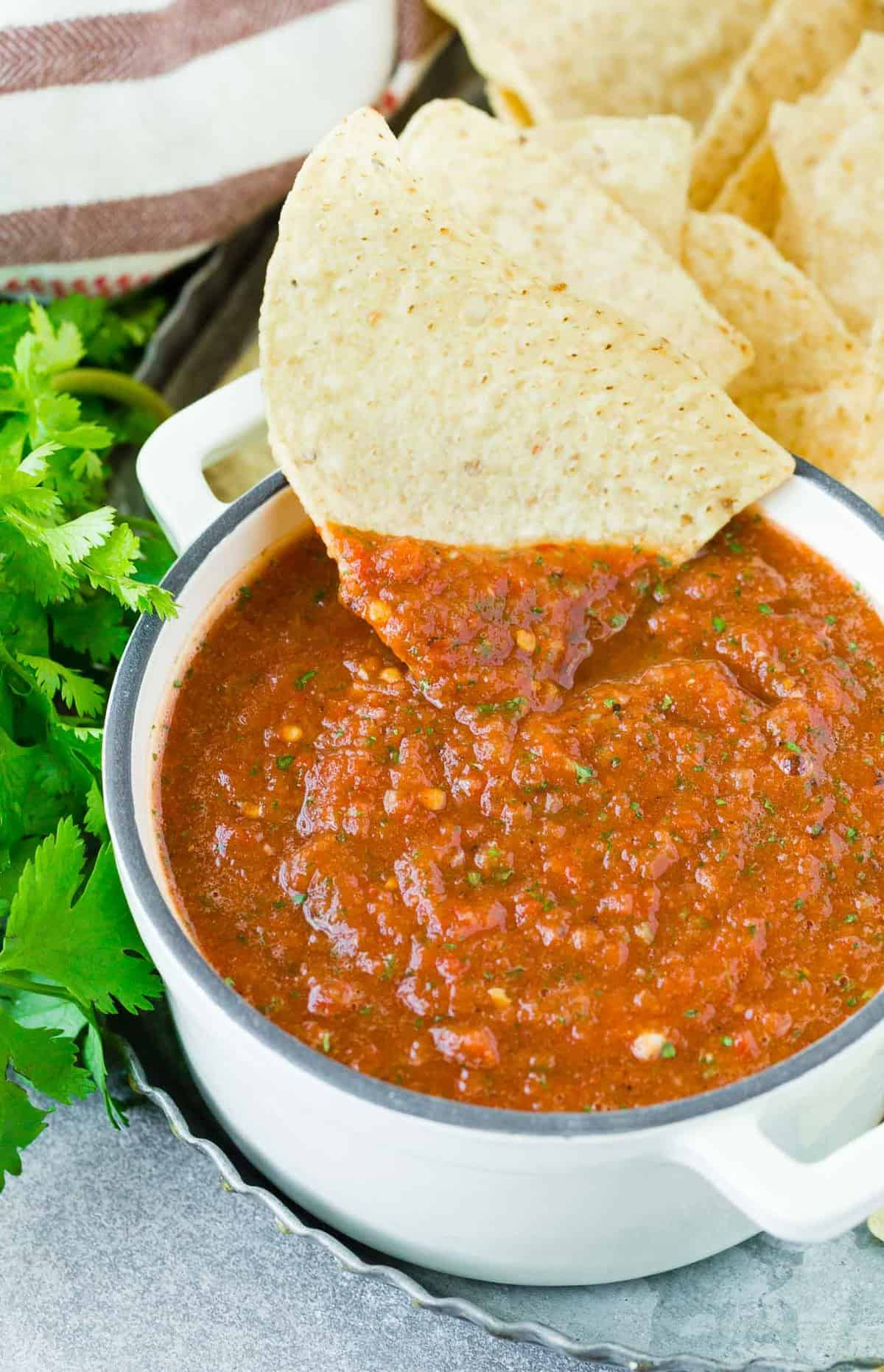 Tortilla chip being dipped into a bowl of salsa.