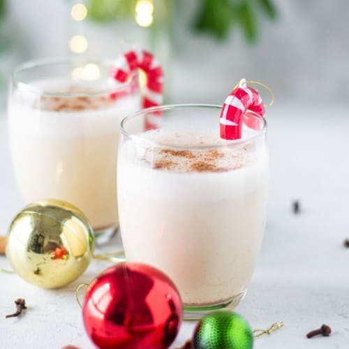 Two small glasses of egg nog garnished with candy cane ornaments.