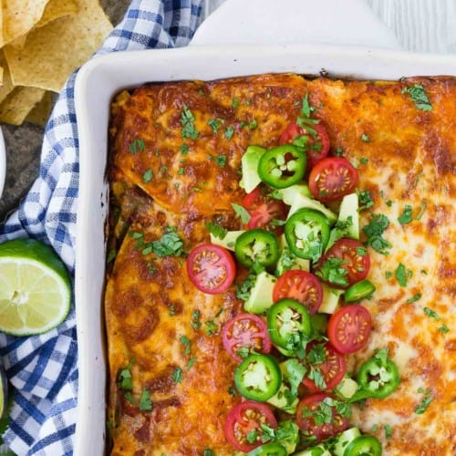 Close up of healthy mexican lasagna topped with avocado, tomato, and jalapeno.
