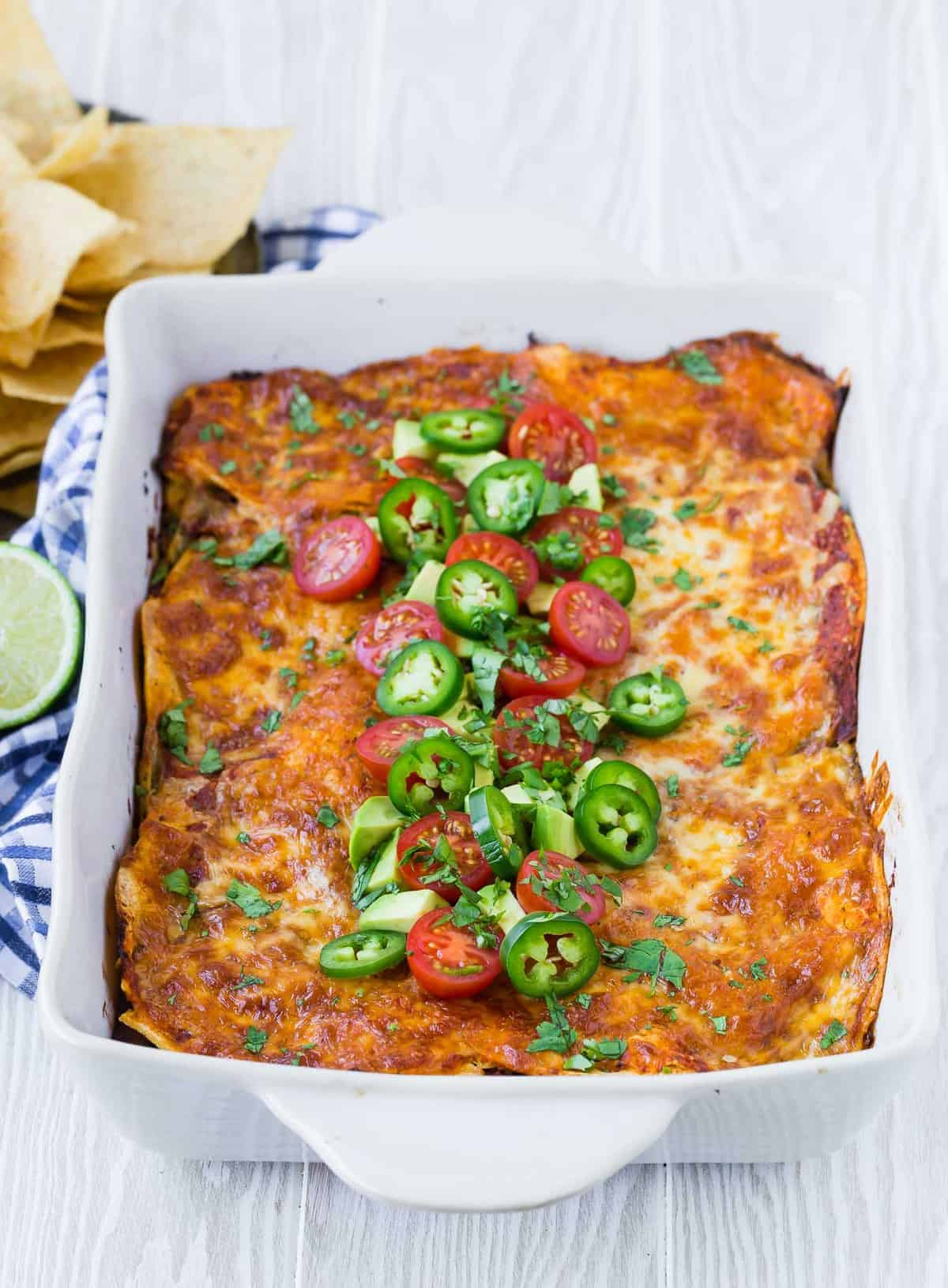 Casserole dish of healthy mexican lasagna with southwestern garnishes.