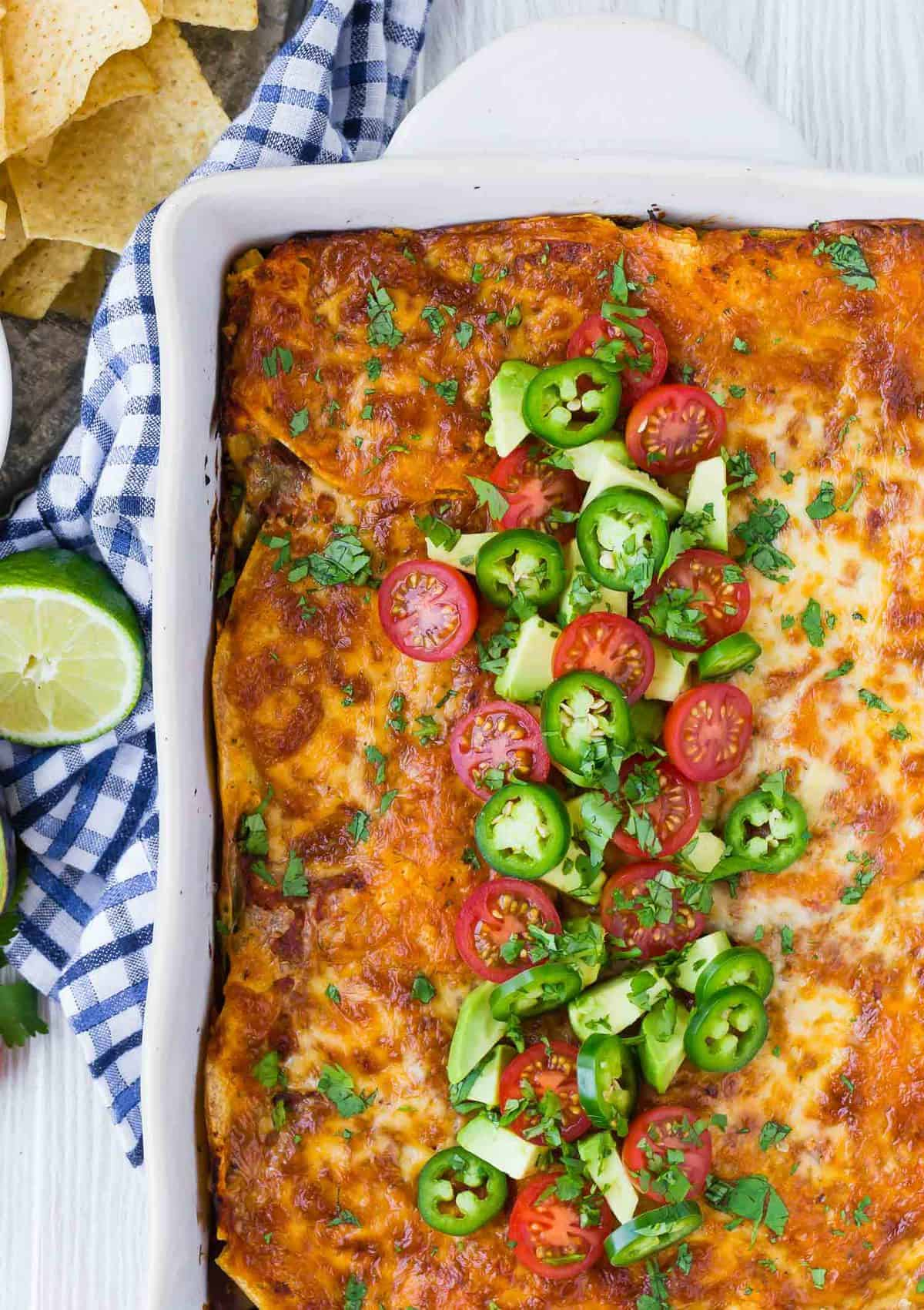 Overhead view of colorful casserole, topped with fresh tomatoes, jalapeno, and avocado.