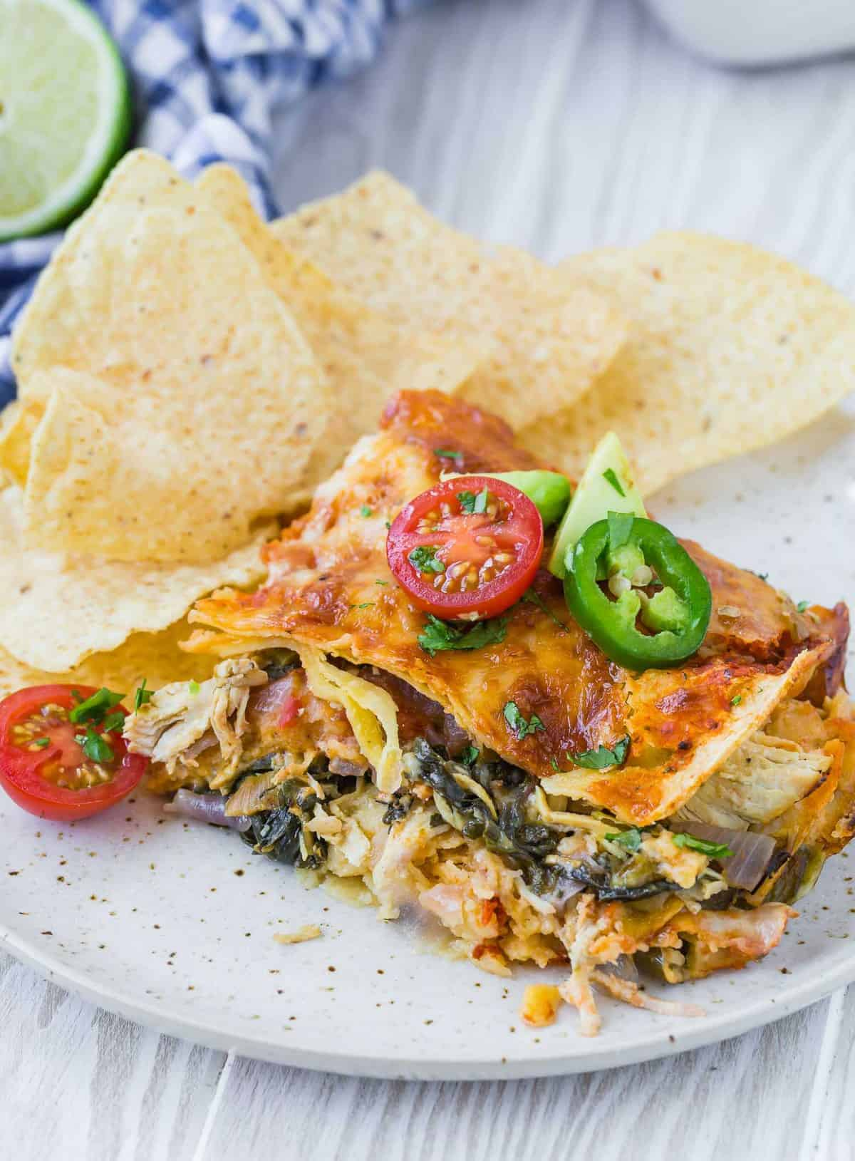 Slice of Mexican lasagna with greens on a plate with tortilla chips.