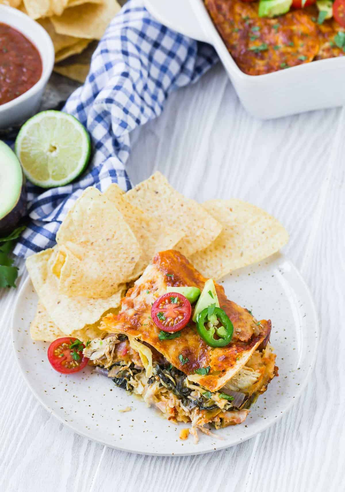 A slice of a layered casserole with tortillas, cheese, and greens, on a plate with chips.