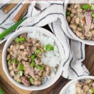 "Beans, rice, and ham topped with green onions in small white bowls. Text overlay reads ""hoppin' john (black eyed peas & rice), rachelcooks.com"""