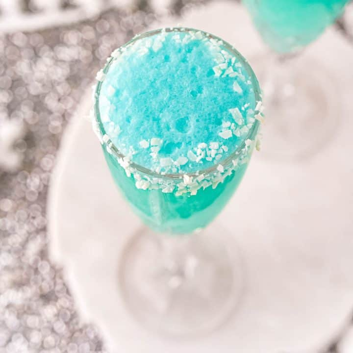 A bright blue mimosa with a coconut rim in a champagne glass.