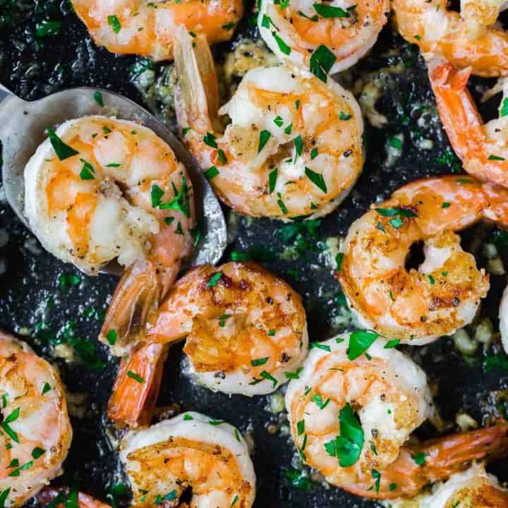 Lemon pepper shrimp in a black pan.