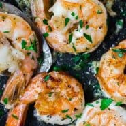 "Cooked shrimp in a pan, text overlay reads ""the best lemon pepper shrimp, rachelcooks.com"""