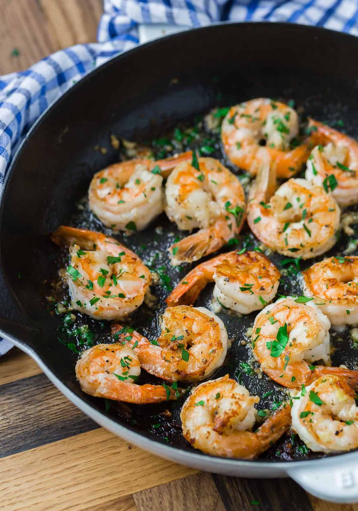 Cooked shrimp garnished with fresh parsley.