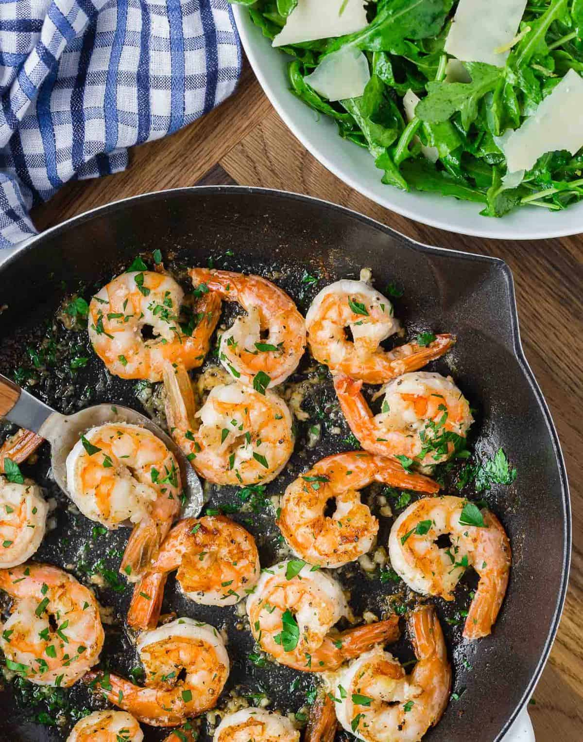 Cooked shrimp in a skillet, a green salad is partially visible.