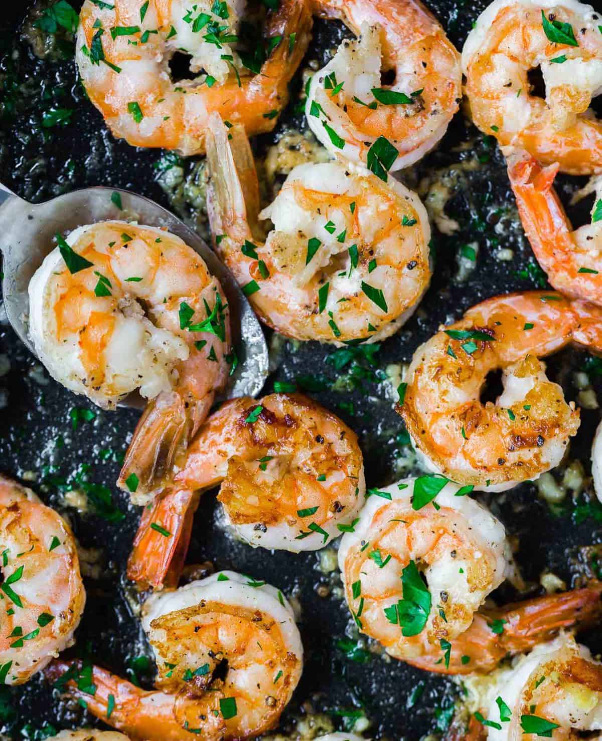 Close up of cooked shrimp in a black skillet.