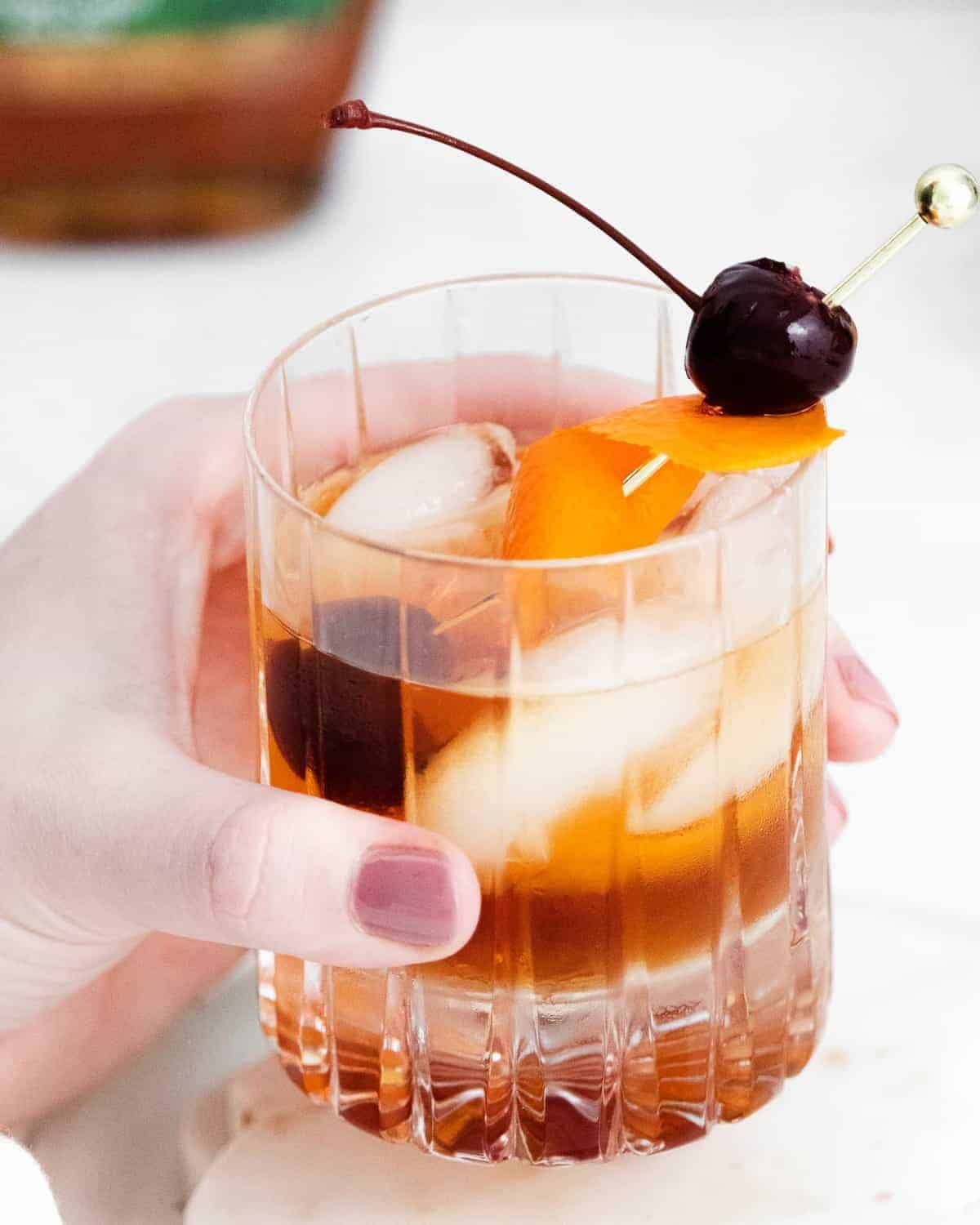 Old fashioned cocktail in a female's hand.