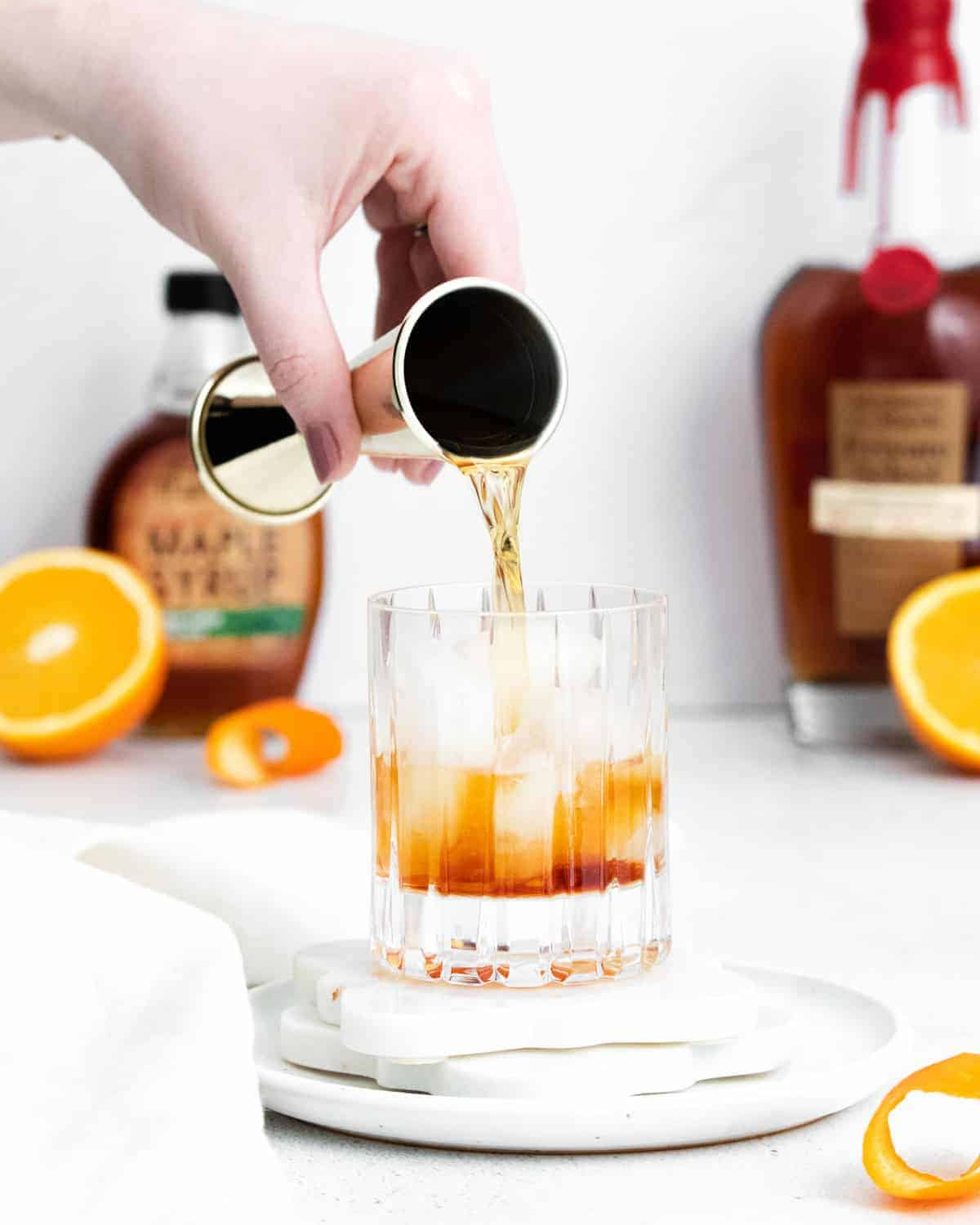Alcohol being poured over ice in an old fashioned glass.