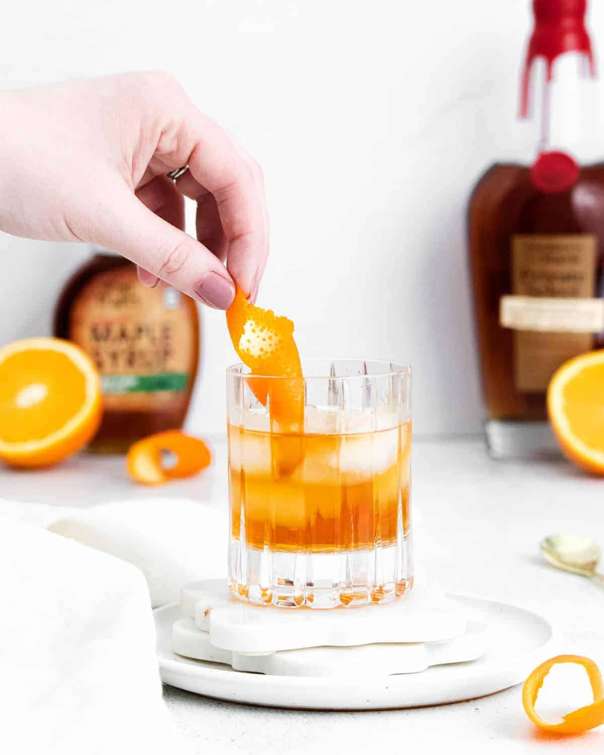 Orange peel being added to an old fashioned cocktail.