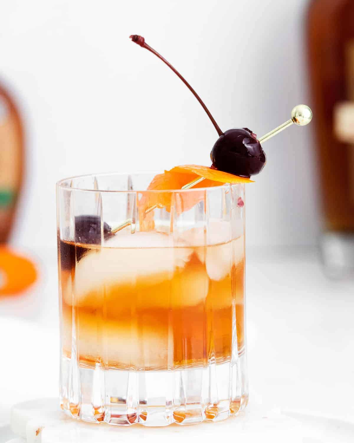 Short cocktail glass with ice, orange peel, cherry, and whiskey.