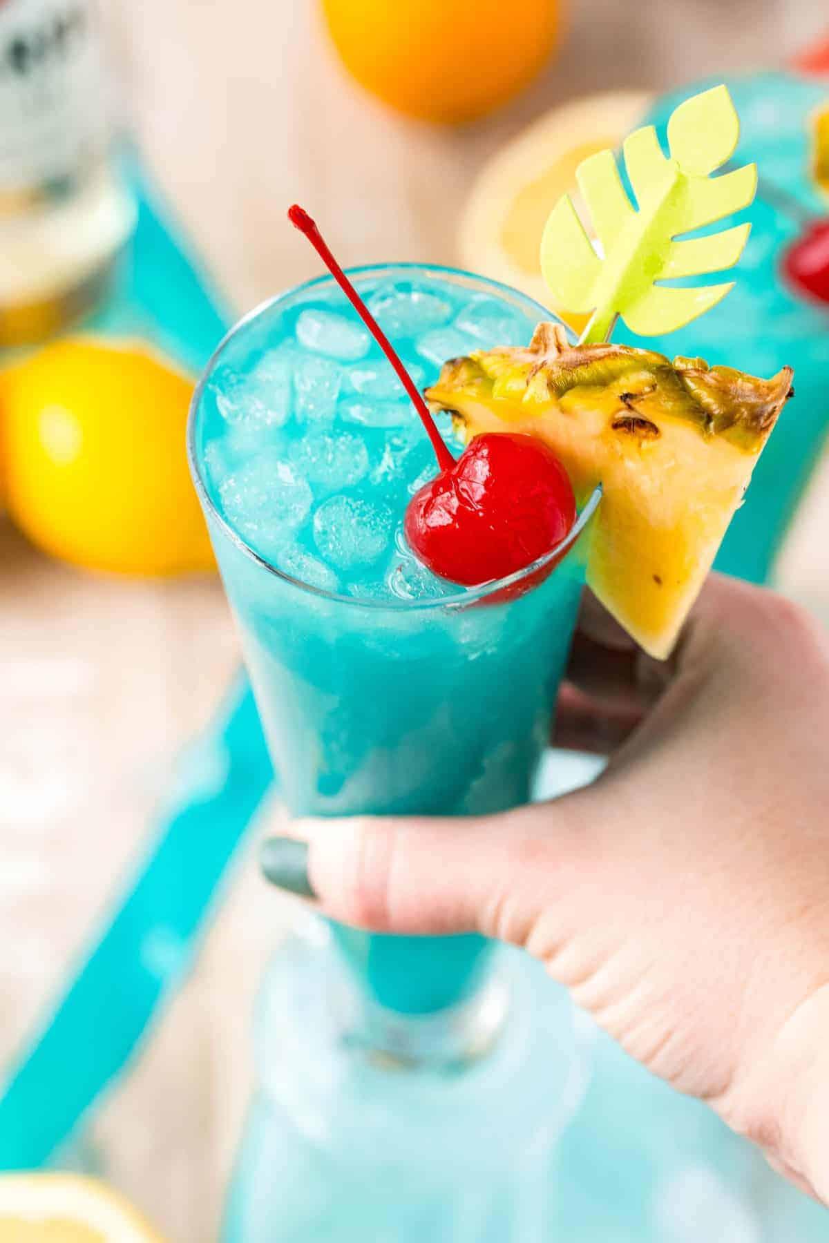 Hand holding a festive bright blue mermaid lemonade.