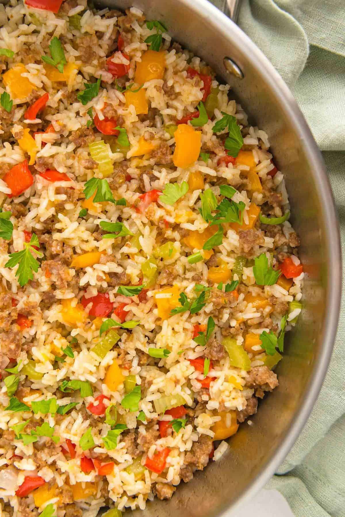 Cooked sausage, rice, and vegetables in a pan.