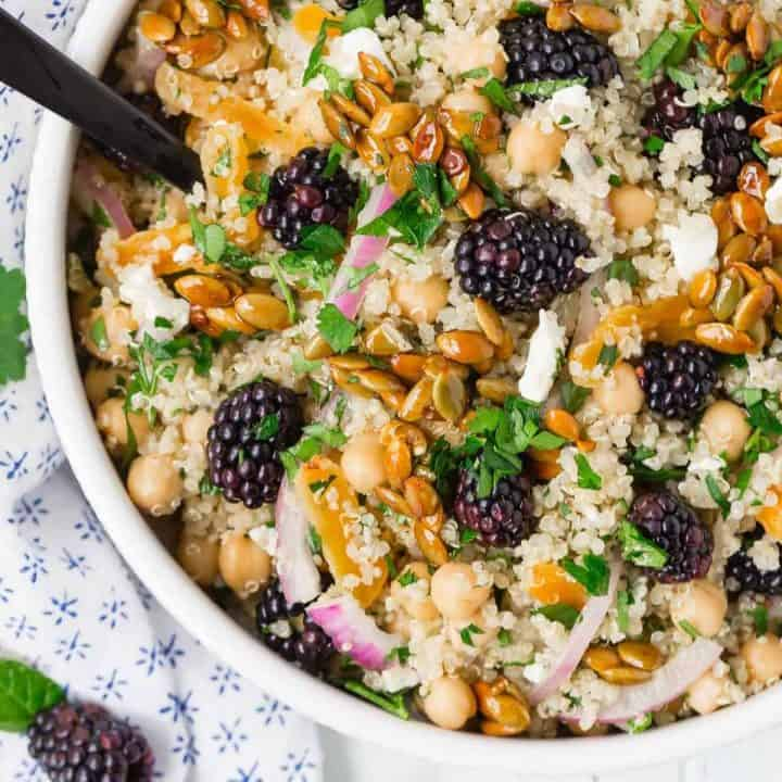Colorful quinoa chickpea salad with blackberries, candied pepitas, onions, feta, and fresh herbs.