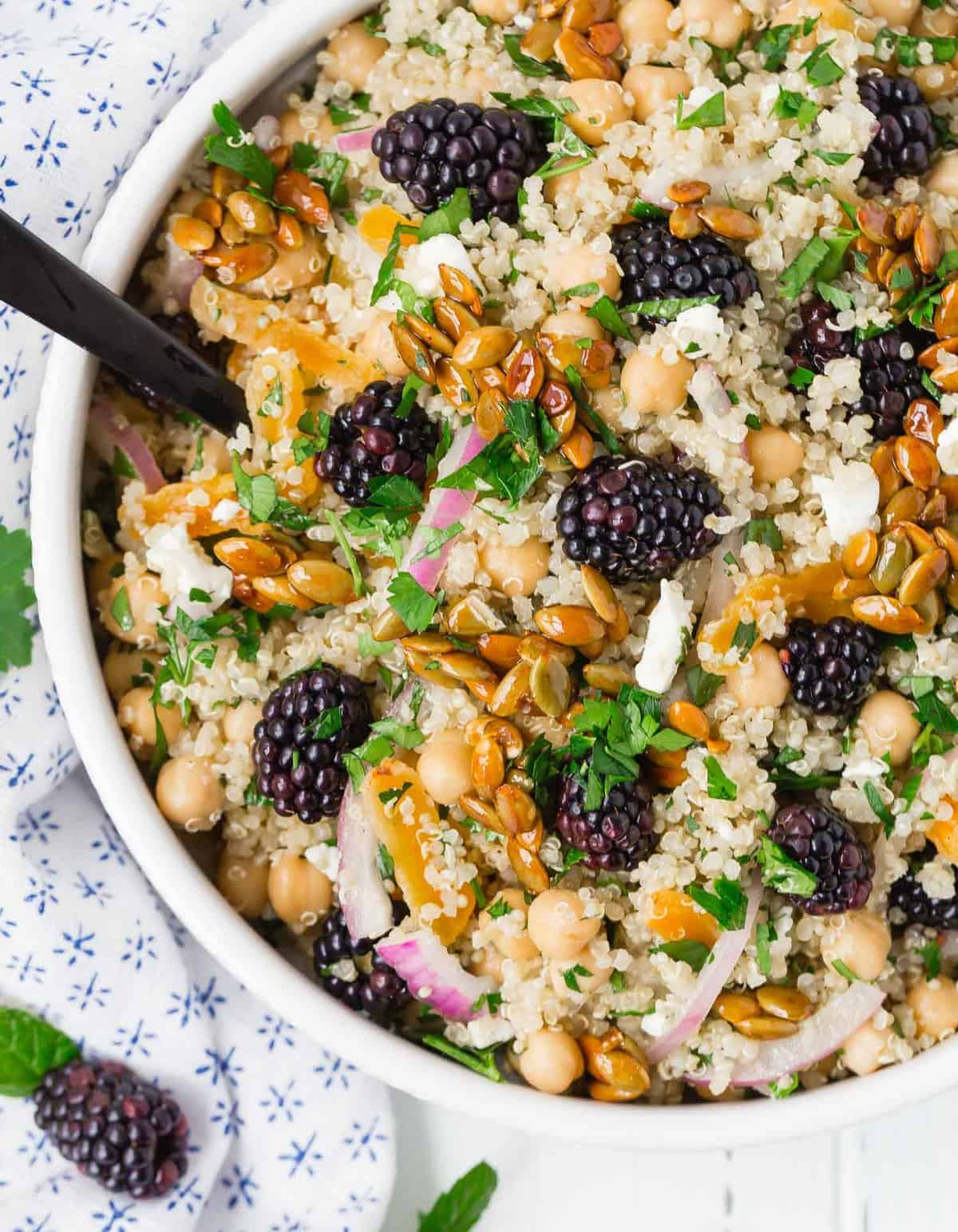 Close up of a salad in a white bowl comprised of quinoa, chickpeas, feta cheese, red onion, blackberries and more.