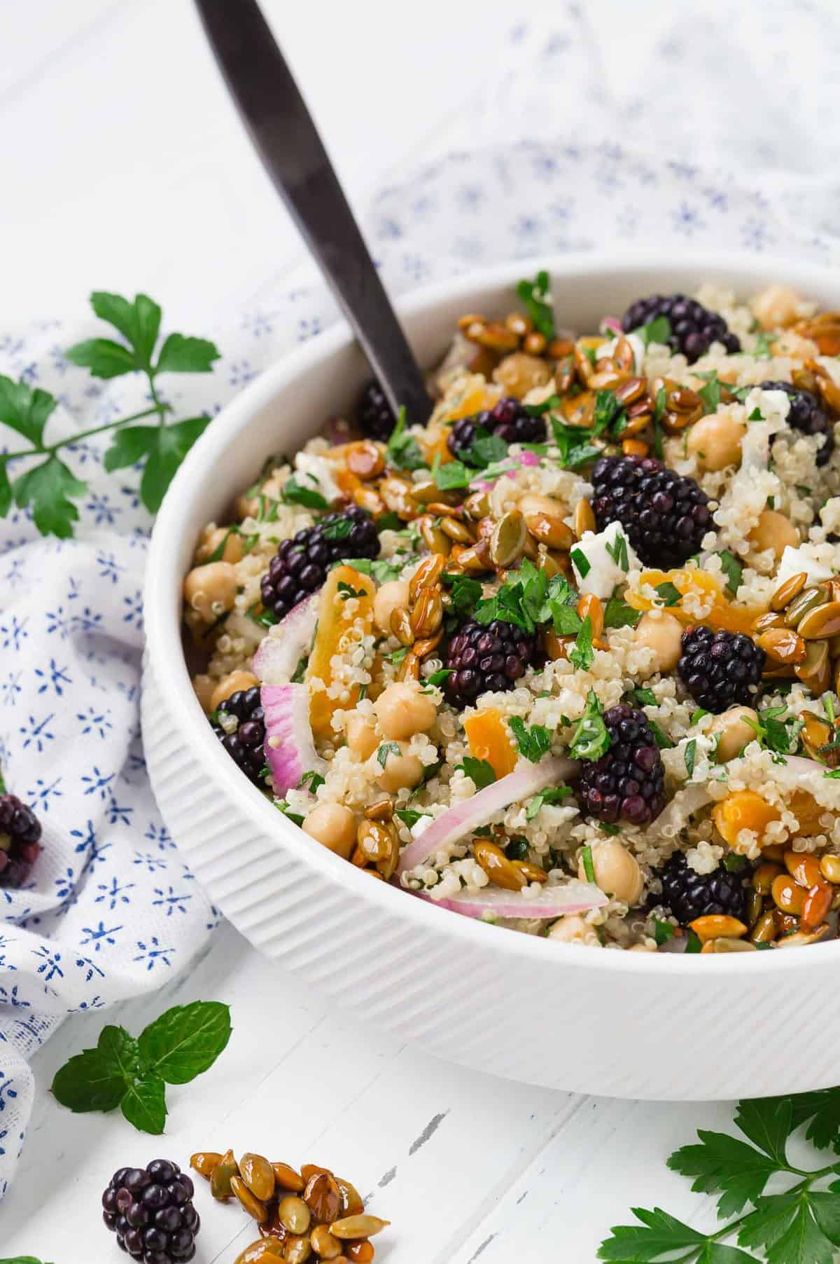 Hearty quinoa salad in a white bowl with a black spoon.