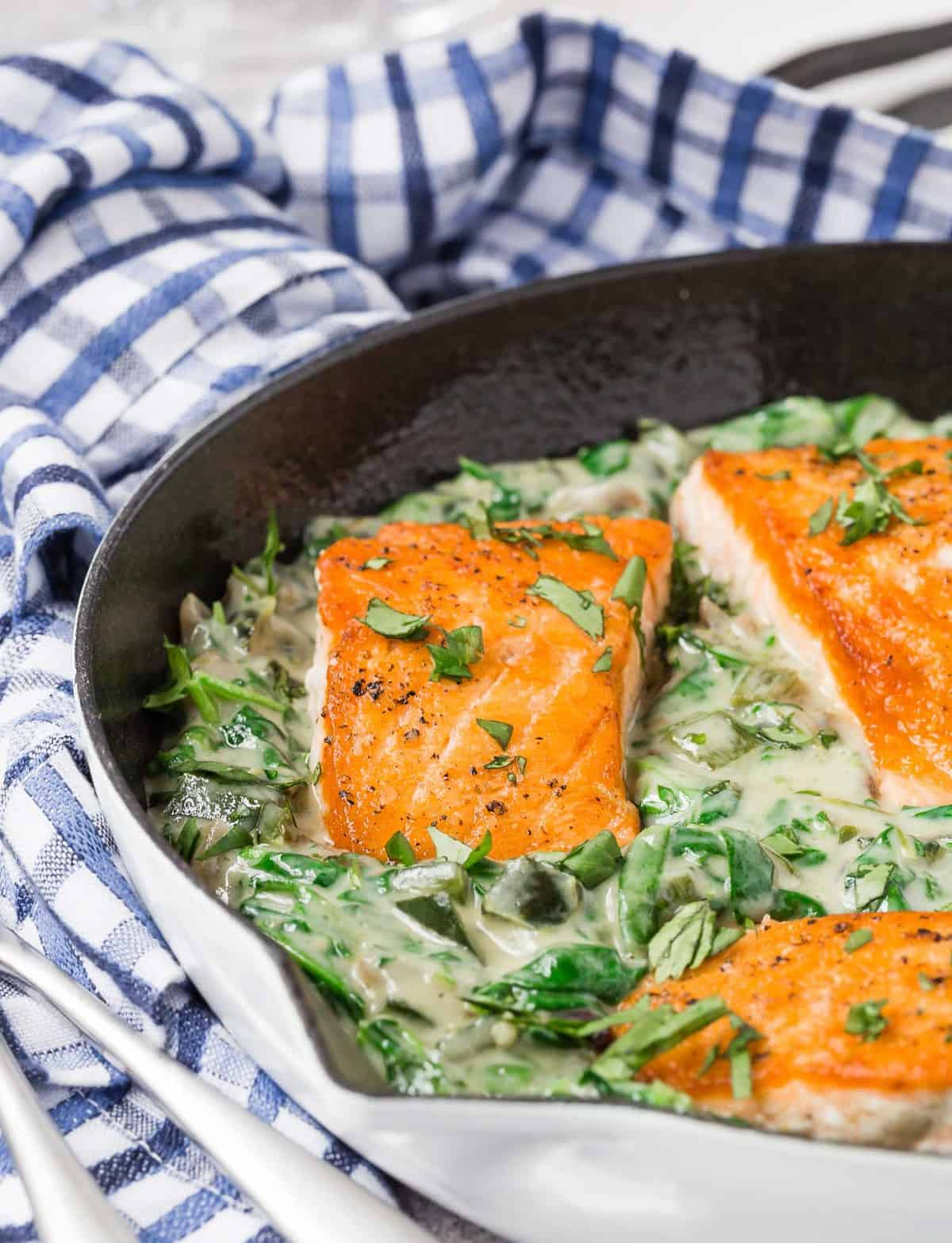 Salmon fillets nestled in a bed of creamy spinach sauce.