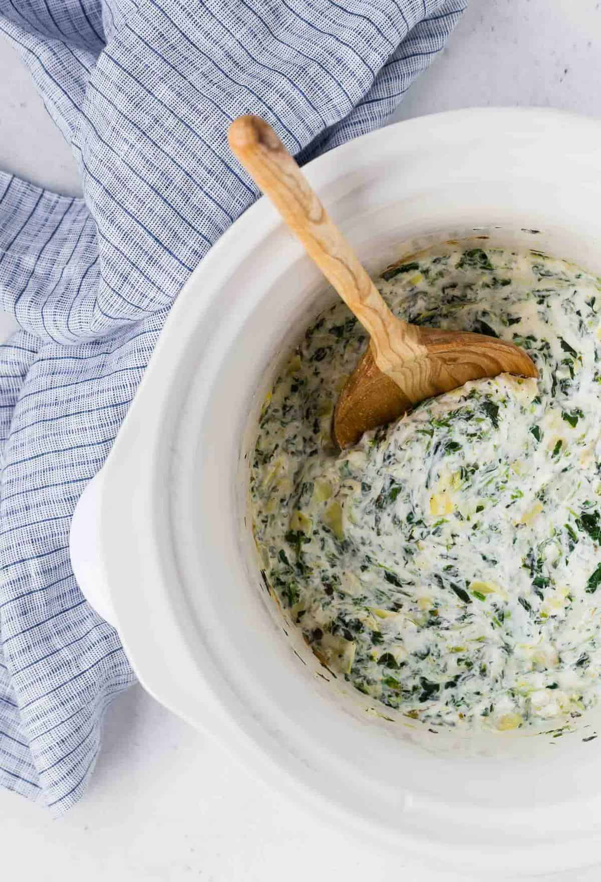 Overhead view of spinach artichoke dip in a white slow cooker.