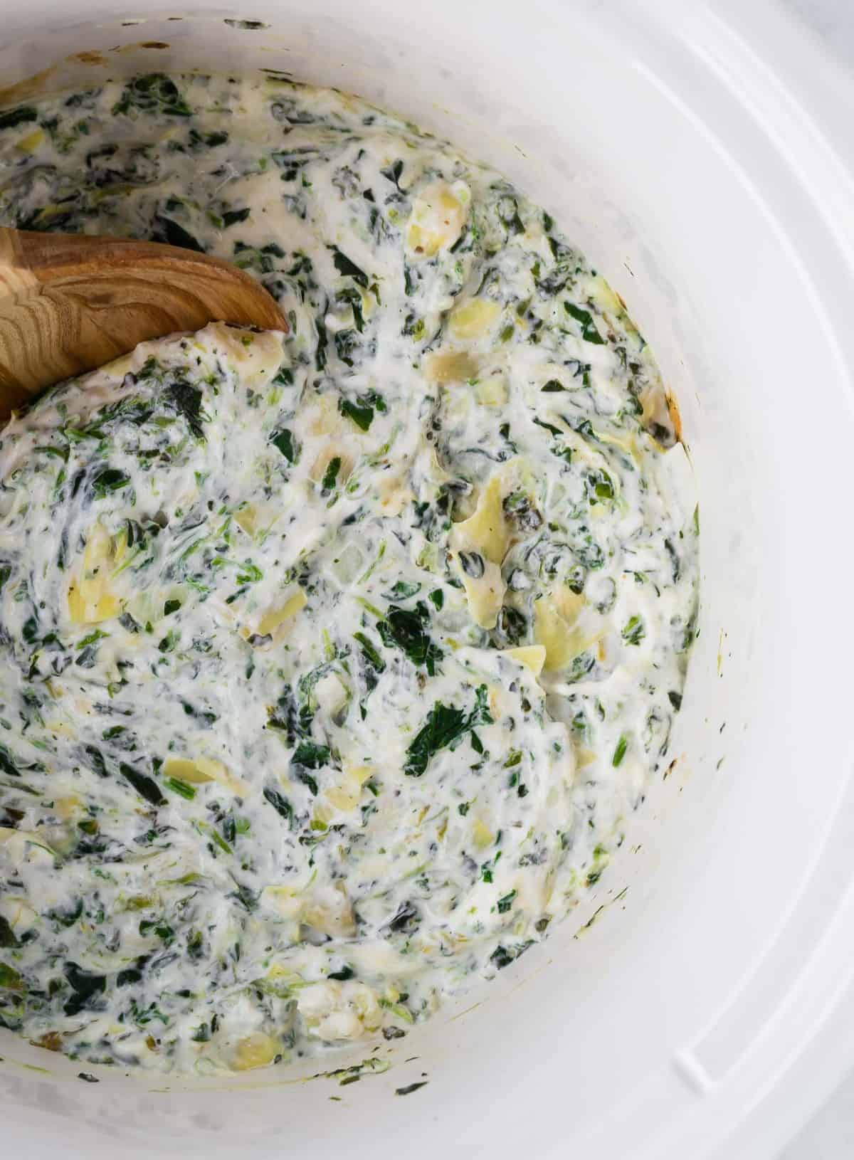 Overhead view of spinach dip with artichoke hearts in a white slow cooker with a wooden spoon.