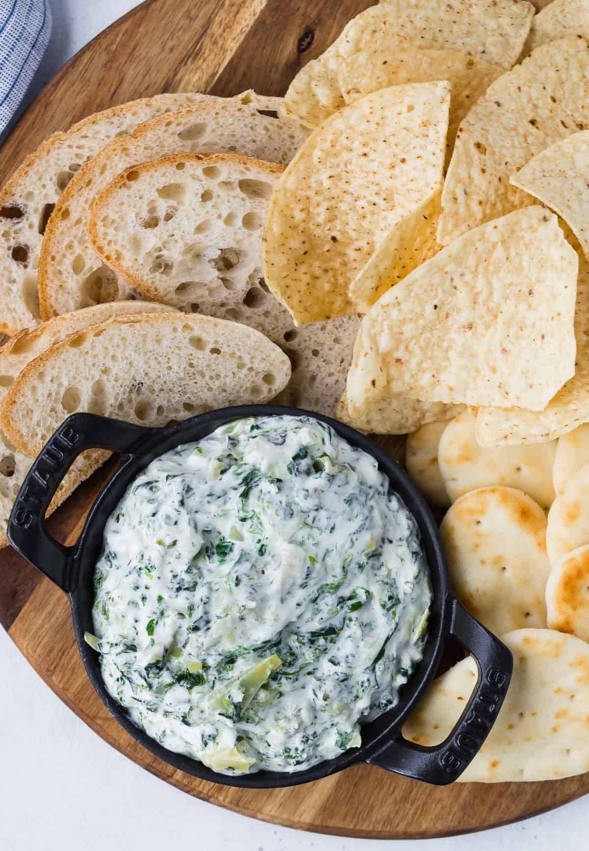 Overhead view of a small black dish of dip made with spinach and artichokes, surrounded by chips and bread.