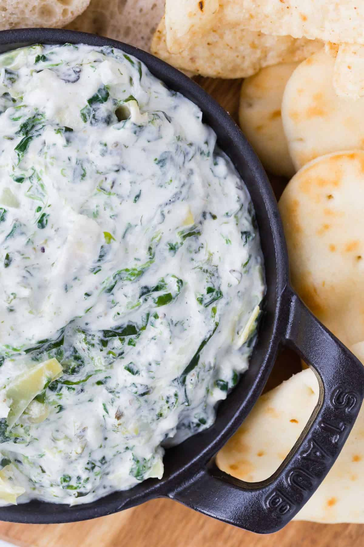 Close up of a creamy dip with spinach and artichoke hearts.