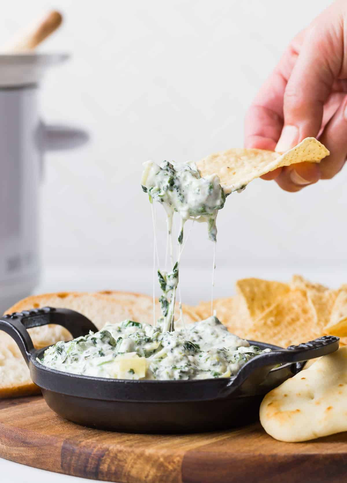 Chip being pulled up from a dish of spinach dip.