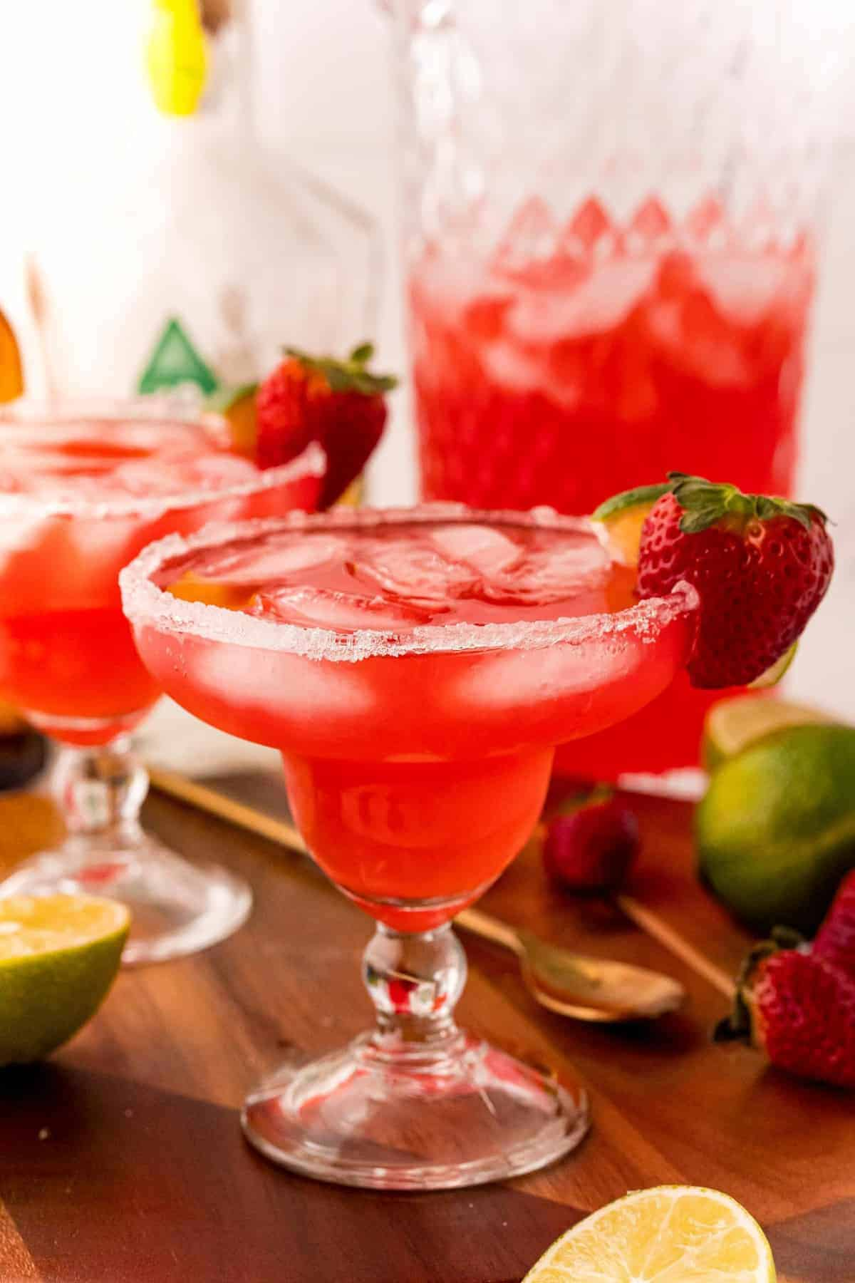 Strawberry margarita punch in a margarita glass in front of a pitcher.