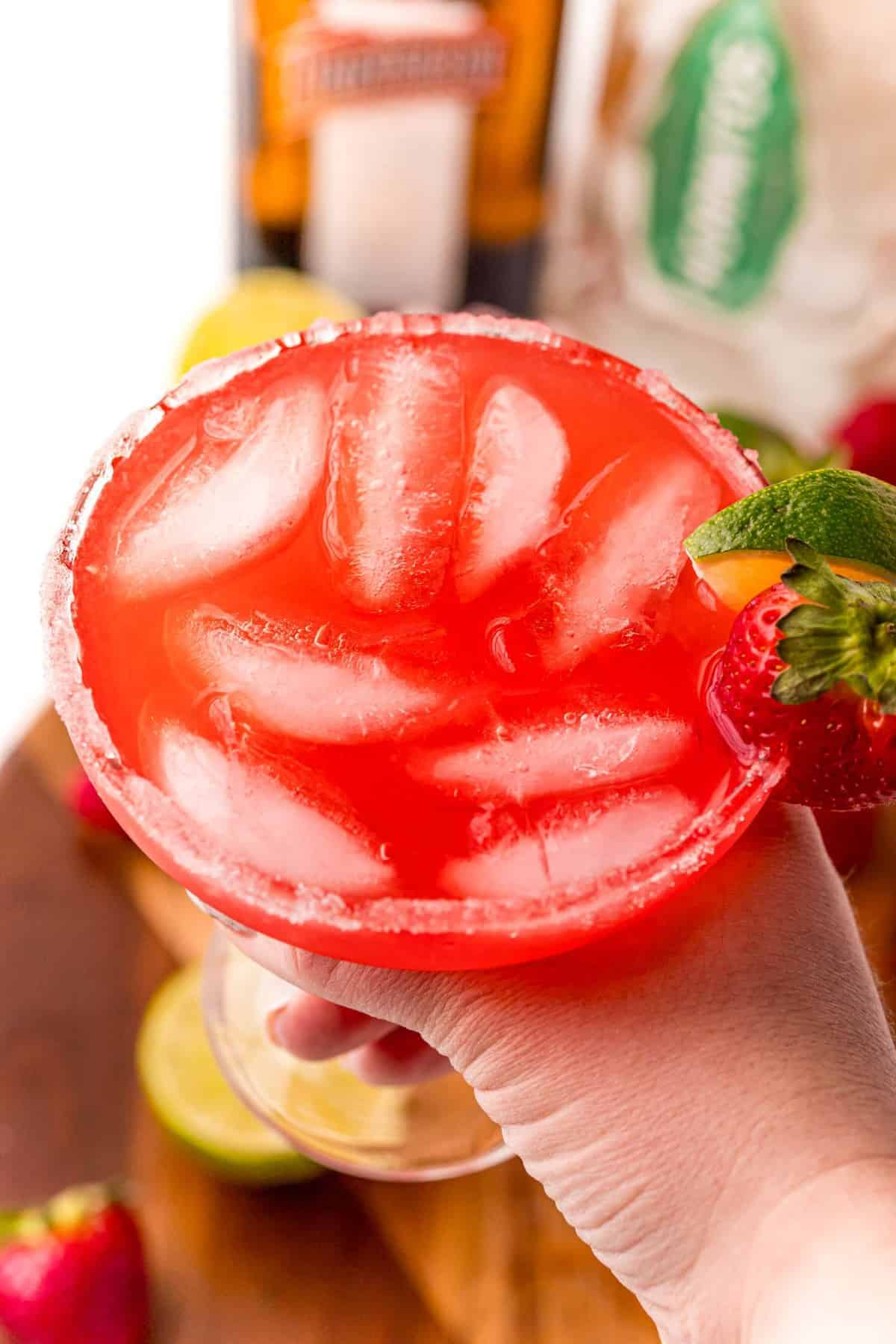 Glass of punch garnished with strawberry being held in a hand.