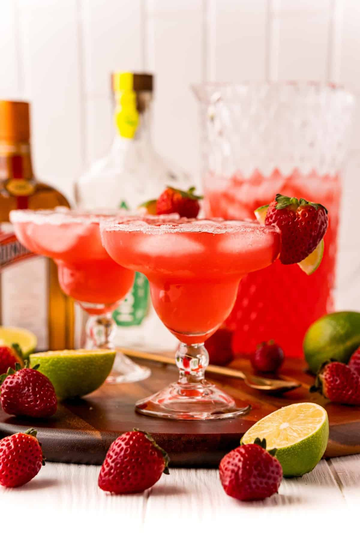 Straight on view of two glasses of strawberry margarita punch. A pitcher and bottles are in the background.