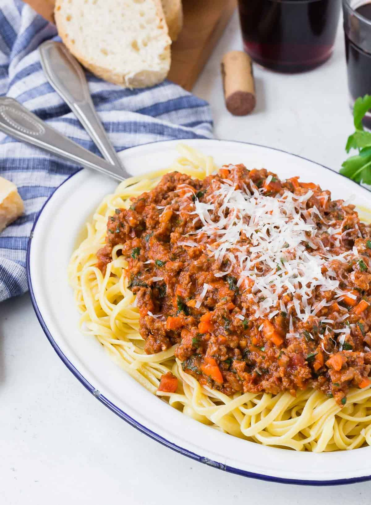 Linguine on a large platter, topped with meat sauce, bread and wine in background.