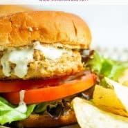 """Close up of a seasoned turkey burger on a whole wheat bun with lettuce and tomatoes. Text overlay reads """"the best easy turkey burger"""""""