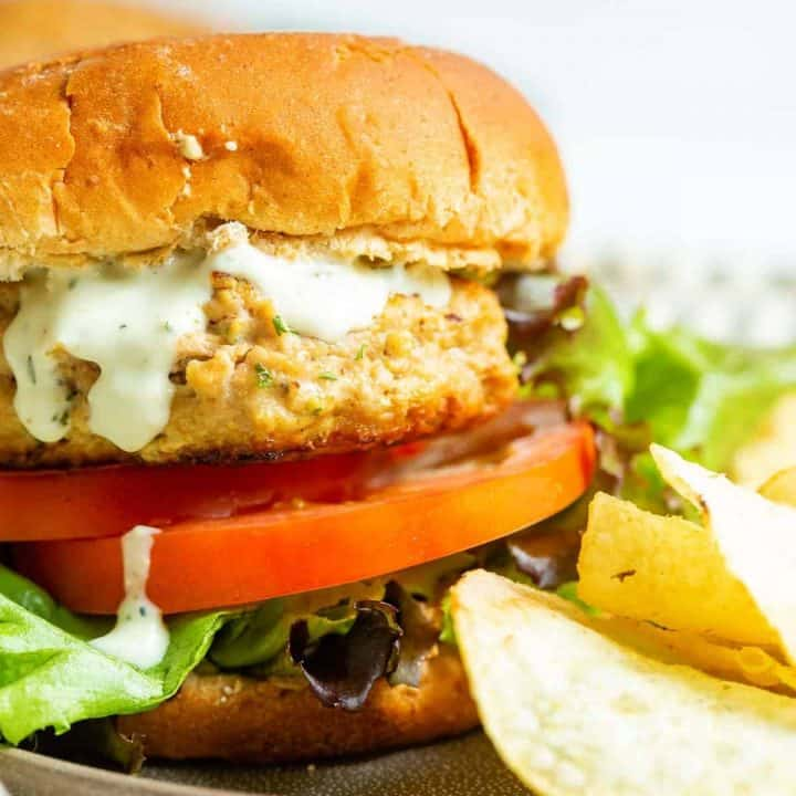 Close up of a seasoned turkey burger on a whole wheat bun with lettuce and tomatoes.