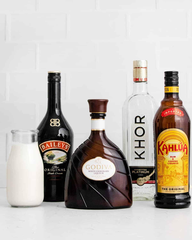 Bottles in a row - milk, bailey's, white chocolate liqueur, vodka, kahlua.