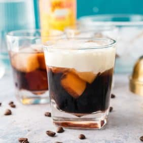 A white Russian cocktail in a short glass, with coffee beans scattered around it.