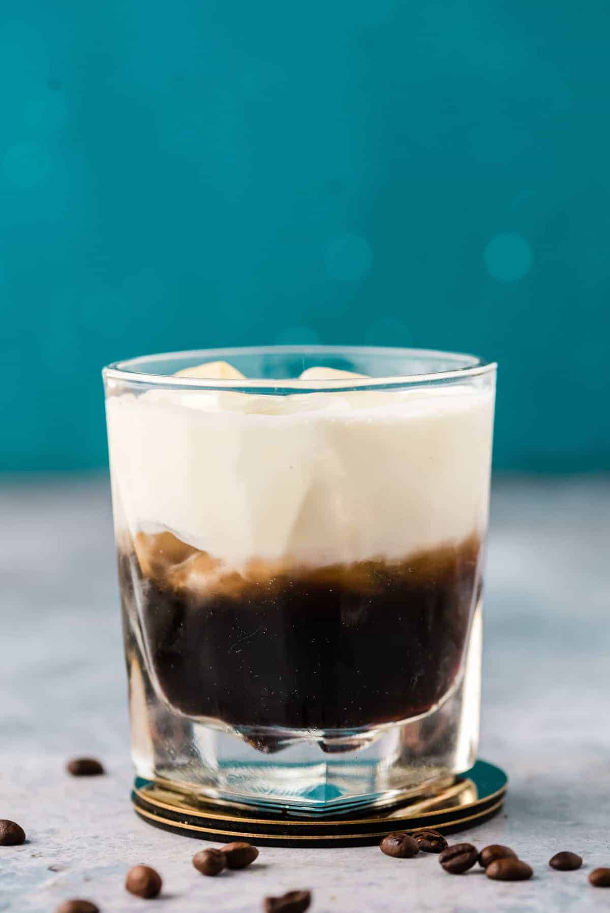 Beautiful layered dark brown and white drink against a blue background.