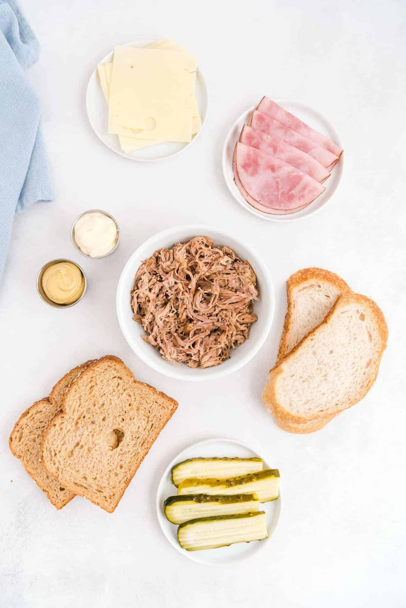 Overhead view of ingredients: pork, ham, pickles, bread, mustard, mayo, cheese.