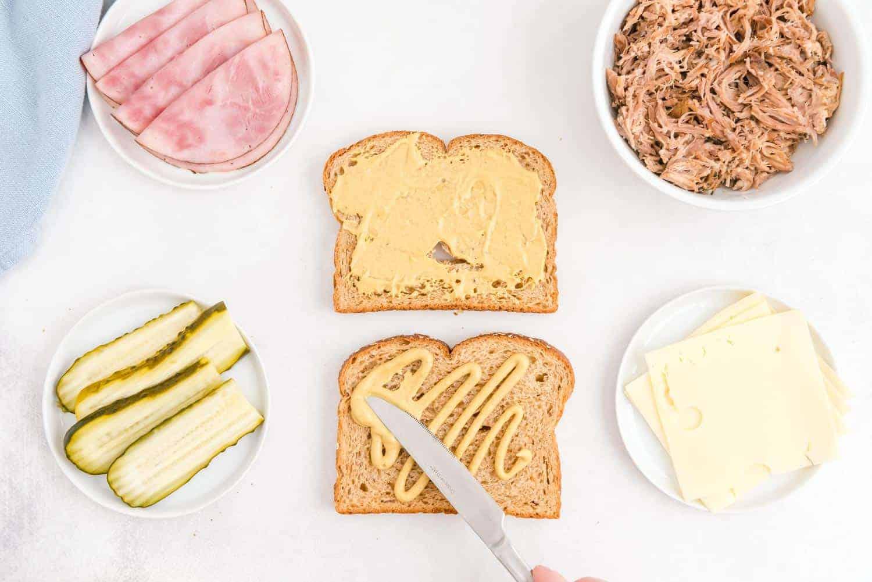 Mustard being spread on bread.