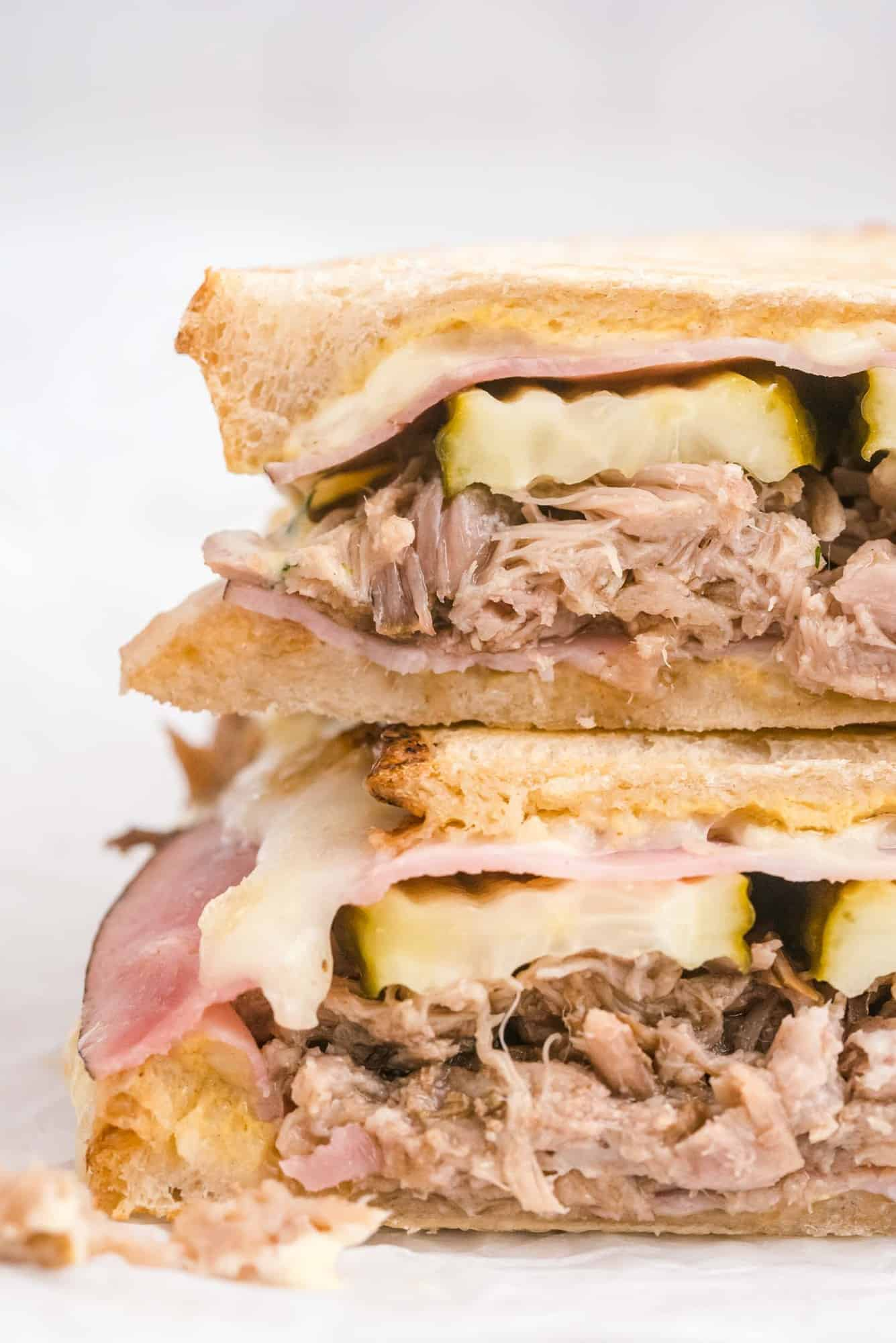 Close up of a sandwich showing layers of pork, pickles, cheese, and ham.