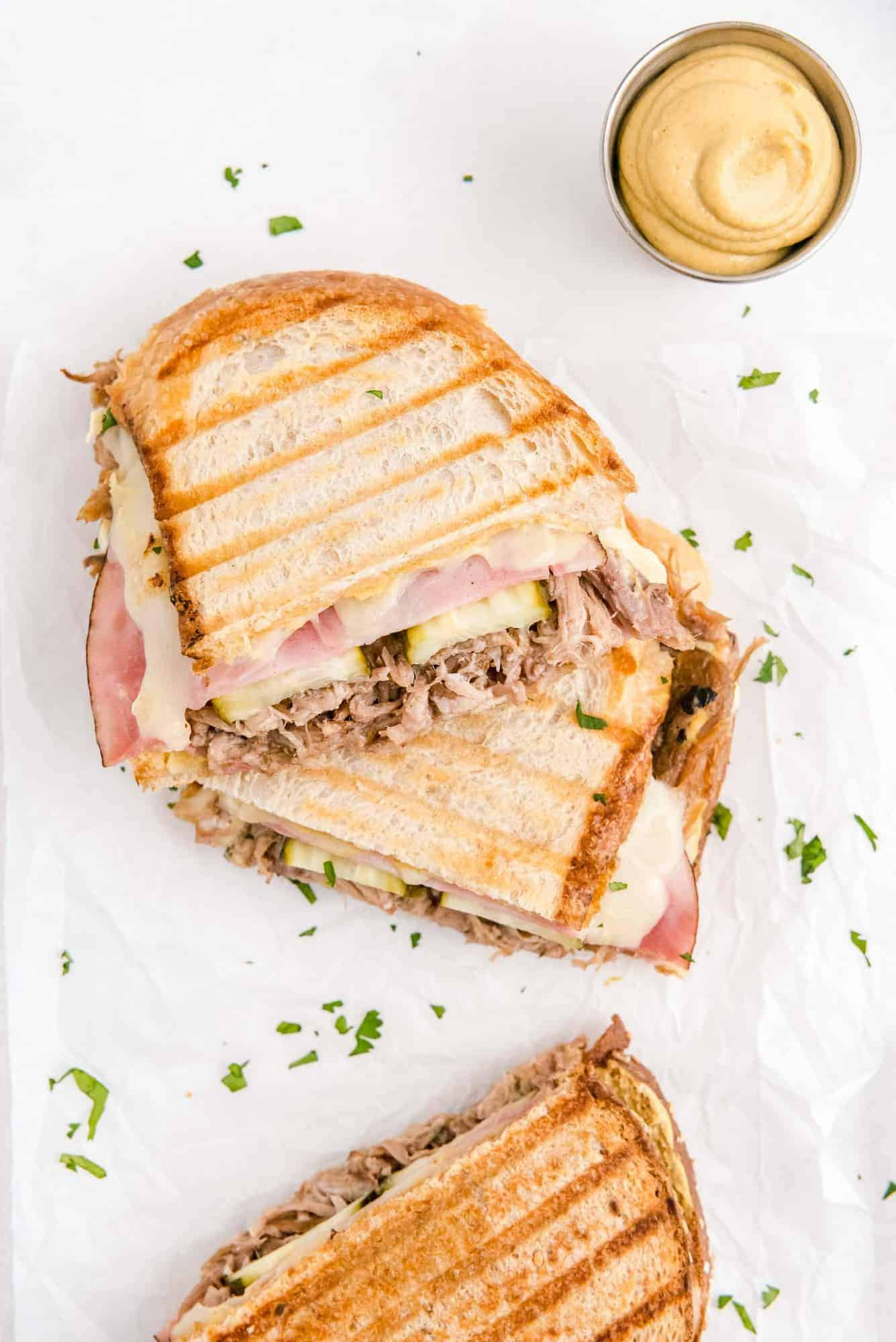 Overhead view of a cuban sandwich, cut in half, with a dish of mustard nearby.