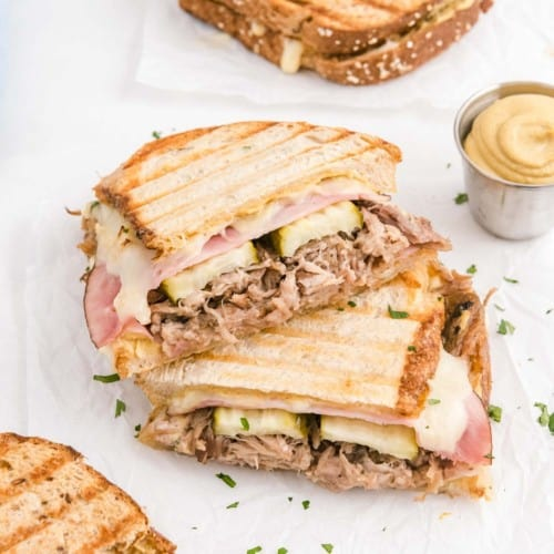 Cuban panini sliced in half, halves stacked on top of each other, on a white surface.