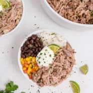 Pulled pork in a bowl with rice, black beans, corn and sour cream.