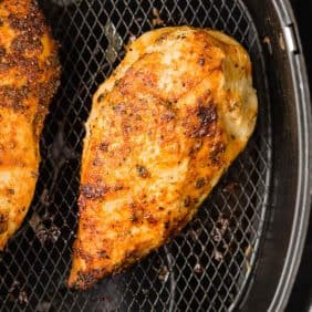 Cooked chicken breast in the basket of an air fryer.